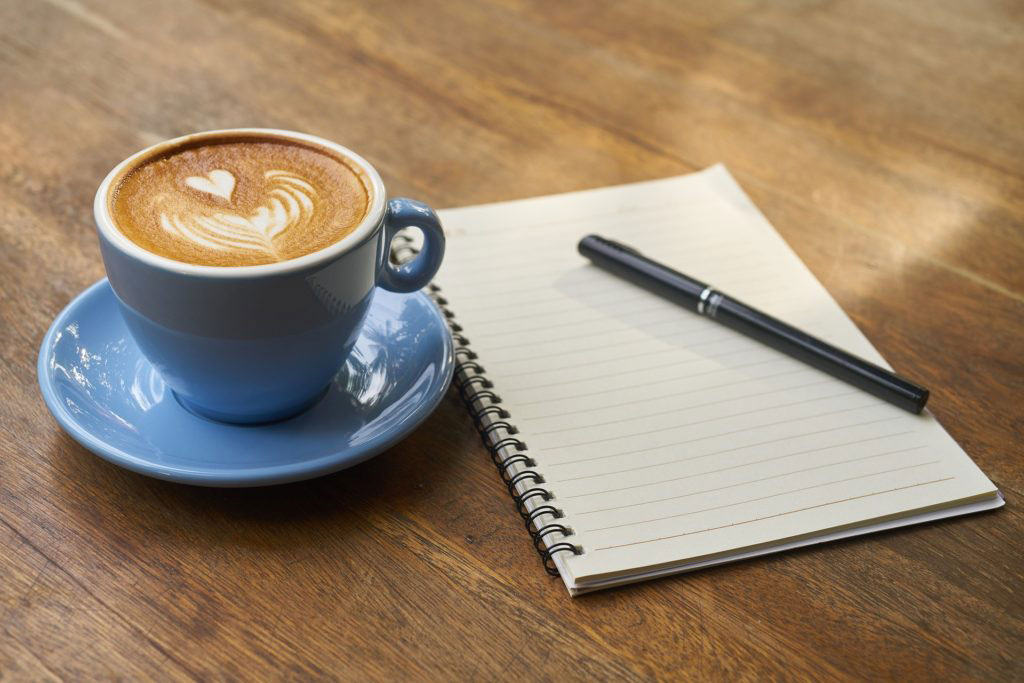 Coffee next to a pad and pen