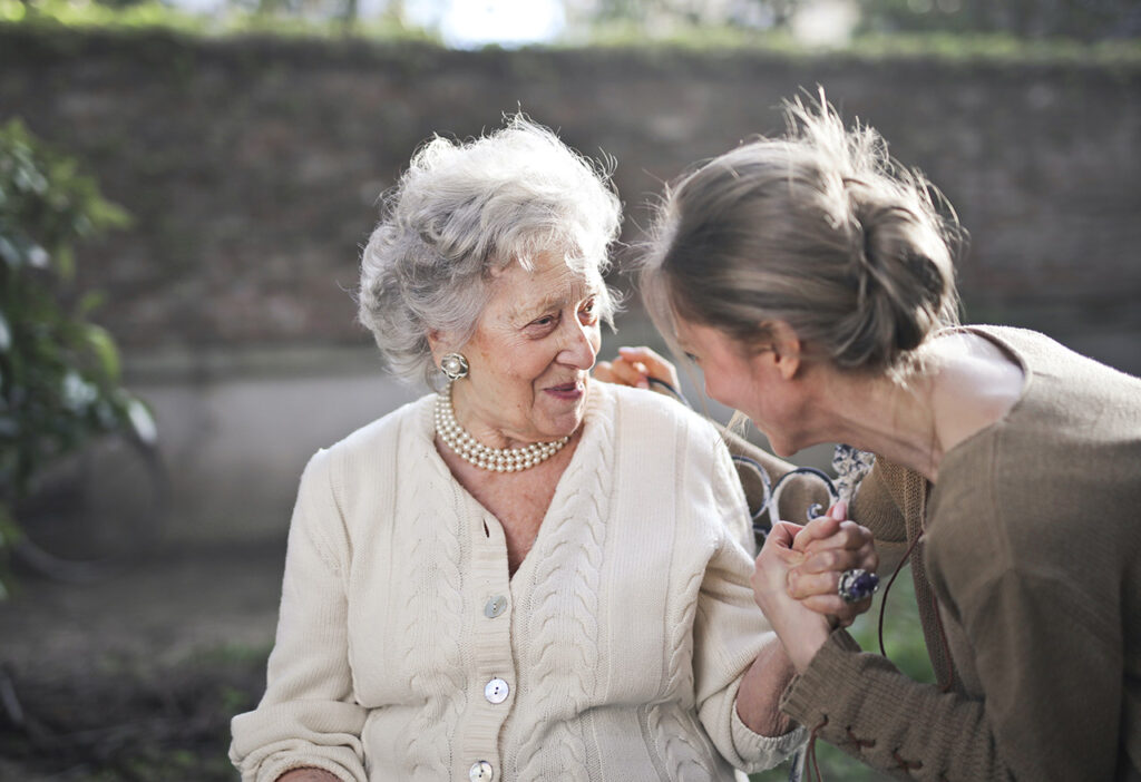 Woman in senior living talking to a friendly hospitality worker